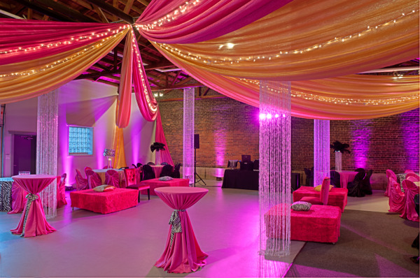 Draping festivities event rental decor floral swagged style ceiling draping in starburst pattern featuring pink and orange chiffon panels with twinkle junglespirit