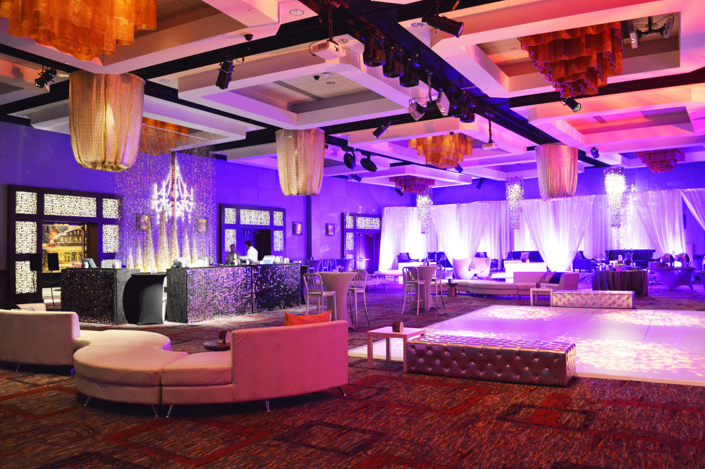 We created a sleek club out of a standard ballroom for this New Year's Eve party. Lounge furniture, gobos, chandeliers, draped VIP areas, sparkle bar front, and more.