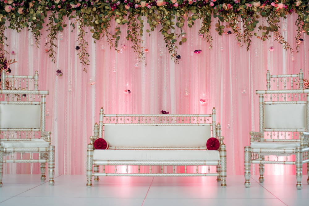 This Pakistani wedding showcases a white stage/flooring, blush draped backdrop with glass beaded curtains and hanging teardrop vases, and a cascading fresh floral band.